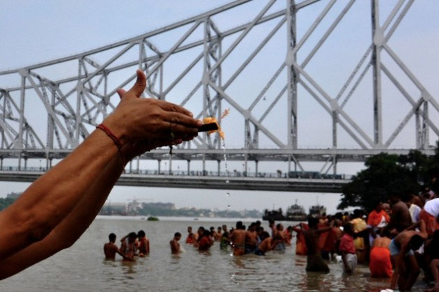 Tarpan being offered on the banks of the Ganges, Howrah Bridge in the background. Image courtesy: Corbis